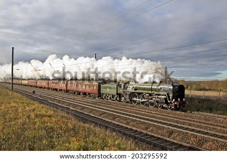 PETERBOROUGH, UK - DECEMBER 7: Vintage steam loco Oliver Cromwell heads the Lindum Fayre excursion toward Lincoln city through rural South Midlands countryside on December 7, 2013 in Peterborough - stock photo