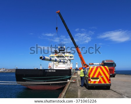 Peterhead, Scotland, 9th of June 2014, Offshore supply vessel loading heavy equipment in harbor for transportation to offshore oil rig. - stock photo