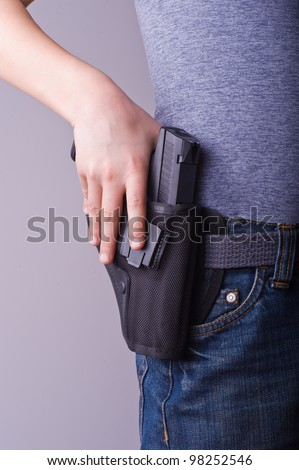 Petite woman carrying holstered gun - stock photo