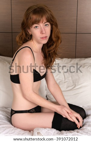 Petite young Irish redhead in black lingerie - stock photo