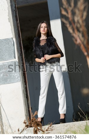 Petite young woman with very long hair wear heels white pants bodysuits and lamb fur vest - stock photo