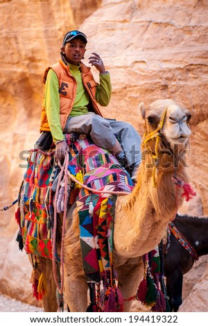 PETRA, JORDAN - APR 29, 2014: Unidentified man rides over a camel in Petra. The city of Petra was lost for over 1000 years. Now one of the Seven Wonders of the Word