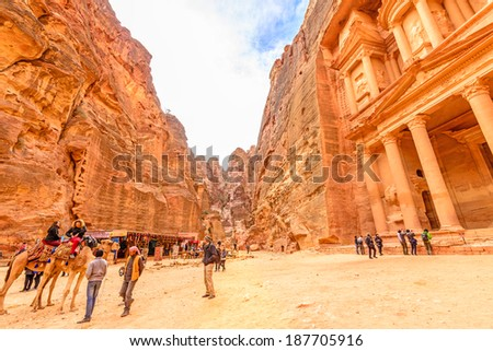 PETRA, JORDAN - DECEMBER 30: Al Khazneh in the ancient Jordanian city of Petra, Jordan on December 30, 2013. It is known as The Treasury and has led to its designation as a UNESCO World Heritage Site. - stock photo