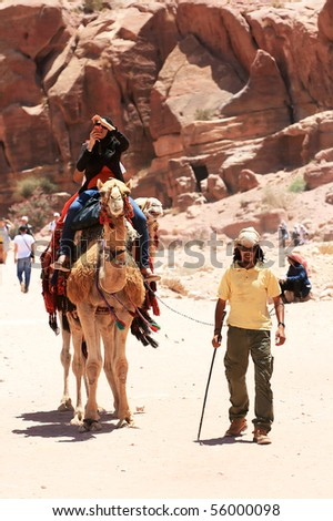 PETRA, JORDAN - JUNE 18: A tourist rides a camel and taking photos in beautiful Valley June 18 in Petra, Jordan. Cameleer walking next to the camel. - stock photo