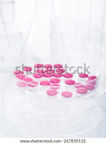 Petri dish with pills in research lab - stock photo
