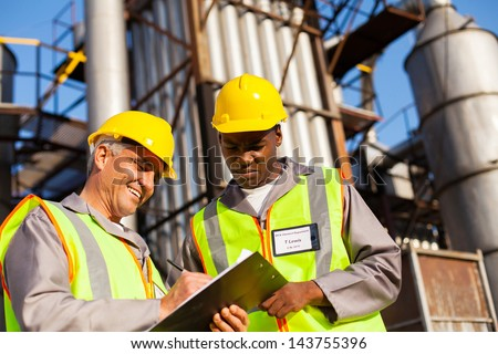 petrochemical co-workers working at refinery plant - stock photo