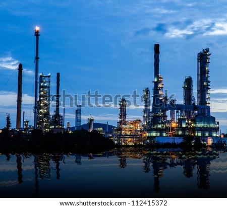 Petrochemical industry on sunset dark blue sky with river shadow.
