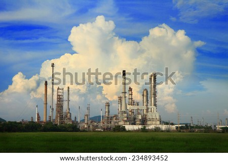 Petrochemical oil refinery industrial plant with cloud and blue sky.