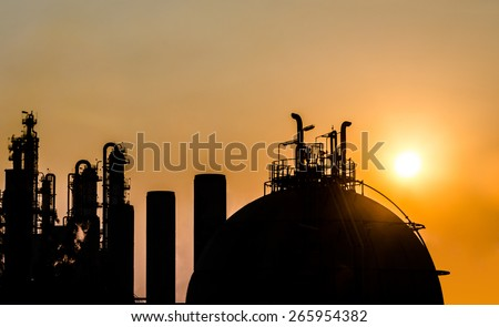 petrochemical plant in silhouette at sunrise - stock photo