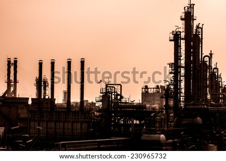petrochemical plant in silhouette image at sun set - stock photo