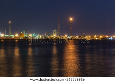 Petrochemical plant reflected light water sunset. - stock photo