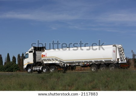 Petrol tanker traveling in the countryside - stock photo