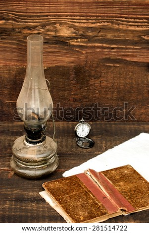 petroleum lamp, old pocket watch and old book  - stock photo