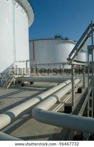 Petroleum storage reservoirs and pipelines are white. Industry object is captured against a blue sky background. - stock photo