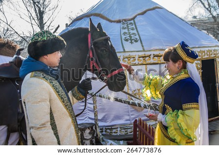 PETROPAVLOVSK, KAZAKHSTAN - MARCH 21, 2015: celebration of the new year on the solar calendar astronomical in Iranian and Turkic peoples. The girl stroking horse