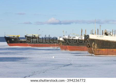 PETROZAVODSK, RUSSIA - MARCH 11TH, 2016: Old frozen cargo ships in the port on Onega lake in winter