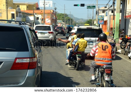 PEURTO PLATA, DOMINICAN REPUBLIC - JAN 22:  A motoconcho (small motorcycle taxi popular in DR) driver negotiates through busy traffic with two young helmetless passengers Jan 22, 2014 in Puerto Plata. - stock photo
