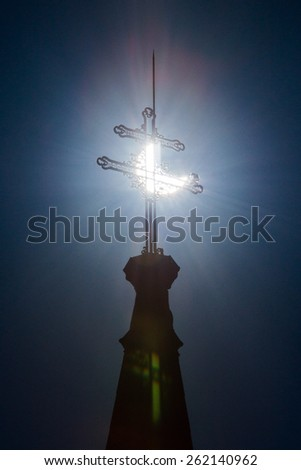 PEZINOK, SLOVAKIA - MARCH 20: Sickle-shaped sun behind a cross during a partial solar eclipse in Pezinok, Slovakia on March 20, 2015 - stock photo