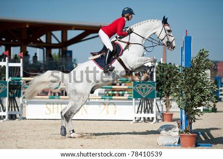 PEZINOK, SLOVAKIA - MAY 29: Jana Miklosova on horse Nourejev N Z jumps over a hurdle at Sharon  Grand Prix CSI1* on May 29, 2011 in Pezinok, Slovakia - stock photo
