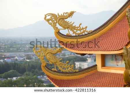 PHAN THIET, VIETNAM - DECEMBER 24, 2015: Fabulous birds on the curves of the roof of a Buddhist pagoda Buu Son