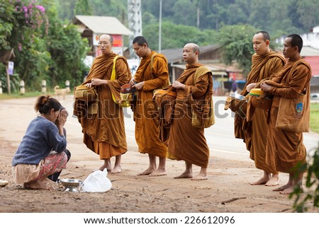 PHANG MAPHA, THAILAND, NOVEMBER 19, 2012: women giving daily food at the Buddhist monks during early morning traditional alms in the village of Phang Mapha, Thailand - stock photo