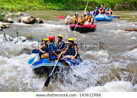 PHANG NGA,THAILAND-DEC 6:Group of tourists enjoy white water rafting on river at Song prack village on December 6,2011 in Phang nga Thailand.Here is the most popular rafting point in South of Thiland.