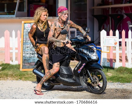 PHANGAN - JANUARY 09 : Unknown guy and girl on motorbike on January 09, 2014 in Koh Phangan, Thailand .Thailand is a magnet for travellers the world over. - stock photo
