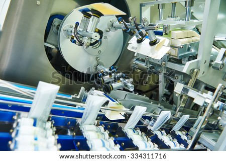 pharmaceutical industry. Line machine conveyer for packaging glass bottles ampoules in boxes at  factory - stock photo