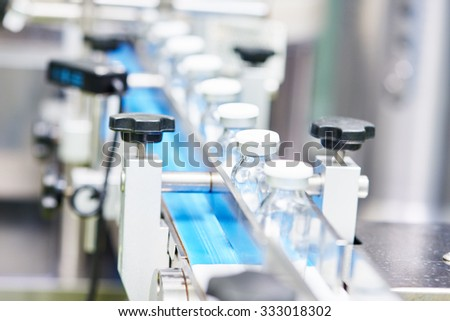 pharmaceutical industry. Production line machine conveyor with glass bottles ampoules at factory, Shallow DOF - stock photo