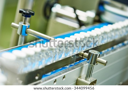 pharmaceutical industry. Production line machine conveyor with glass bottles ampoules at factory - stock photo