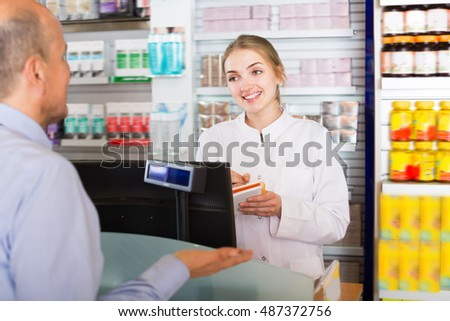 Pharmaceutist in drugstore helping customer to choose medication