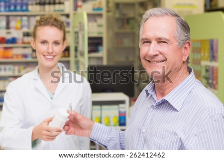 Pharmacist and costumer smiling a camera at pharmacy - stock photo