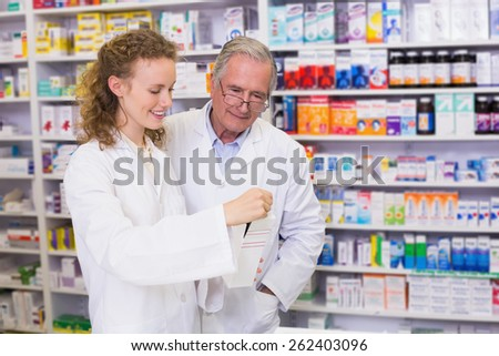 Pharmacist and trainee talking together about medication in the pharmacy - stock photo