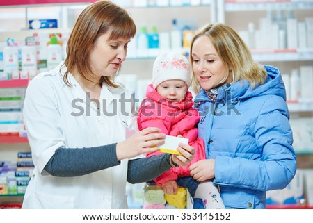 pharmacist chemist woman demonstrating vitamin to child girl with mother in pharmacy drugstore. family health - stock photo
