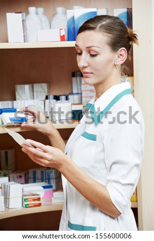 pharmacist chemist woman searching drugs in pharmacy drugstore warehouse - stock photo