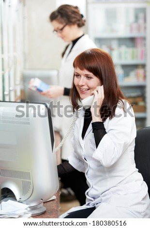 pharmacist chemist women consulting on phone in pharmacy drugstore - stock photo