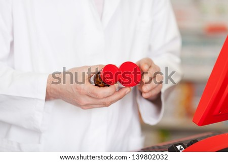 pharmacist comparing medicine bottles - stock photo
