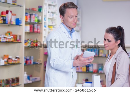 Pharmacist explaining the drug to patient in the pharmacy - stock photo