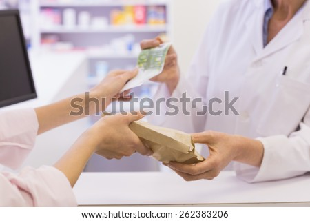 Pharmacist giving medicine to costumer at pharmacy - stock photo