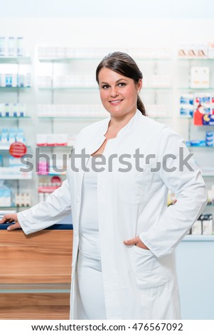 Pharmacist in chemist shop in front of shelves with drugs looking at camera