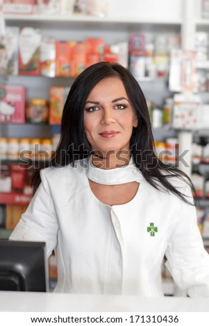 Pharmacist in drugstore, looking at camera - stock photo