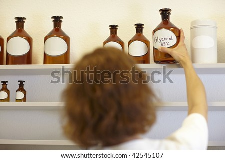 Pharmacist in lab holding bottle with glycerol - stock photo