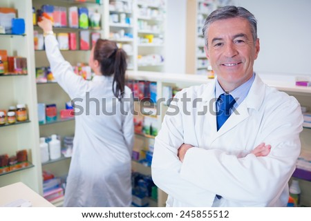 Pharmacist looking at camera with student behind him in the pharmacy - stock photo