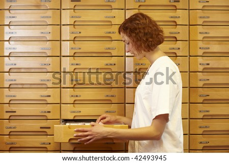 Pharmacist reaching for drawer at medicine cabinet - stock photo