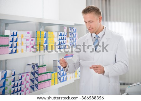 Pharmacist reading label on medicine packet while holding prescription paper at store - stock photo