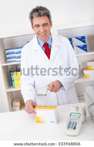 Pharmacist scanning barcode using scanner at drugstore - stock photo