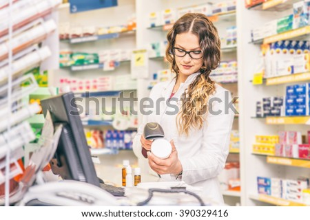 Pharmacist scanning price  on a medicine box - Female doctor working in a pharmacy - stock photo