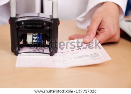 Pharmacist Stamping Prescription At Desk - stock photo