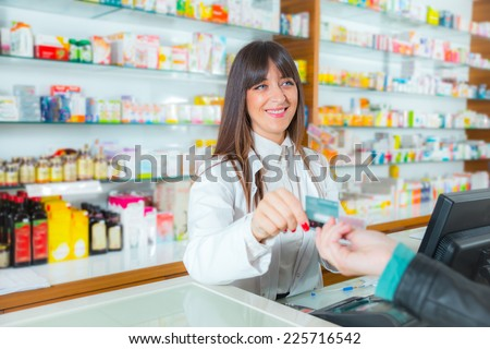 Pharmacist suggesting medical drug to buyer in pharmacy drugstore, customer pays by credit card - stock photo