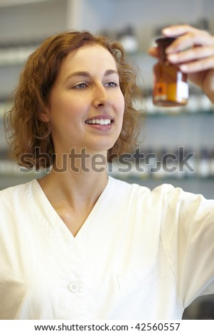 Pharmacist taking a look at Calciumchlorid in pharmacy - stock photo